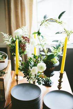 Buffet styling with black Heath Ceramics plates, florals, and tall taper candles.