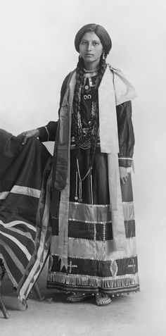 An old photograph of a Native American Girl in Traditional Dress. No name. No date. No photographer.