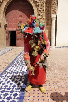 A water seller-This is a dying profession. In ancient Morocco the duty of this profession was to sell water. You can see the water cups around his neck. Today he makes a living by charging tourists money to click his picture.