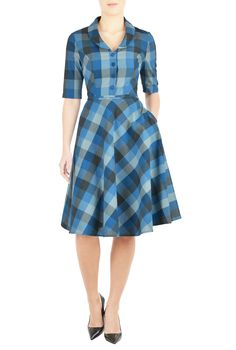 A shawl collar frames the V-neckline of our cotton check dress, nipped in at the waist with self-piped trim and flared out to a full circle skirt.