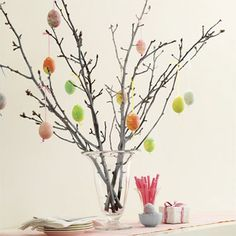 Easter-egg tree. Arrange a selection of tree branches in a vase or metal bucket. These branches were sprayed with white acrylic paint for a softer look. Thread a narrow 1/8-inch silk ribbon through the top of eggshell, thread a bead on the bottom end of the ribbon, and  secure with a knot.