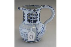 An 18th century Delft puzzle jug, probably Liverpool, painted underglaze in blue with landscapes