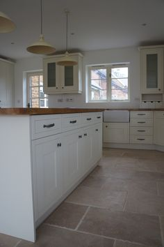 The warm, honey tones of the Rustic Travertine tiles look great against the cream tones of this Shaker kitchen.
