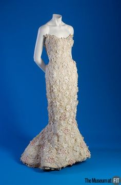 Christian Dior  Ballgown white organdy c.1955   The color choice of white and the subtle use of pink sprinkled around the hemline serve to symbolize Christian Dior's image of a structurally perfected and stylized femininity.