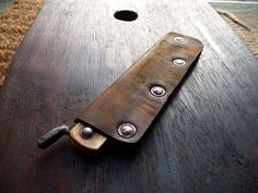 Ru Titley Knives: Custom distressed leather pocket slip for a Japanese Higonokami folding knife. Made from thin veg tan leather, double dyed and distressed with wire wool and fixed with hammered copper saddlery rivets .