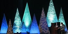 Tiffany Marshall fromGateway Community ChurchinWebster, TX brings us this cool variety of Christmas trees. Theirset consisted of 20 triangular Christmas Trees. 4 - 12'X6' : made with 2X4's 6 - 10'X5' : made with 2X4's 4 - 8'X4' : made with 2X4's 2 - 6'X3' : made with 2X2's 4 - 4'X2' : make with 2X2's They painted the frames white and added bases to the bottom. They used materials such as Saran Wrap/Aluminum Foil/Bubble ...