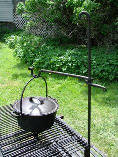 Outdoor cooking, swinging arm cast iron pot hanger