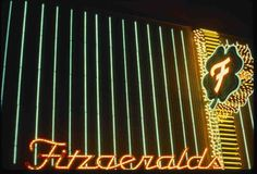 """A color image of neon signs for Fitzgerald's Club in Reno, Nevada, 1986. One of the signs is in the shape of a four-leaf clover with the letter """"F"""" glowing in its center.  Image is part of UNLV Libraries """"Photo"""" digital collection."""