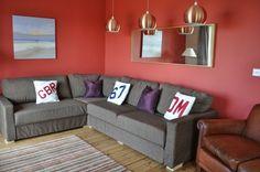 salon avec déco murale en rouge et canapé gris