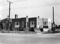 "Original East York Library - 1948 a former residence purchased for a library. 1950: East York Public Library officially opened at the northeast corner of Coxwell and Mortimer avenues, 26 April. Renovation by H. E. Witmer, Architect. Cardinal design by Thoreau MacDonald adopted as the library's logo. 1955: Library Board resolves to build a central library to replace ""the present facilities which have become inadequate,"""