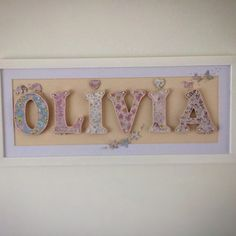 Handmade children's names using decorated wooden letters and framed with a white…