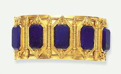 AN ETRUSCAN REVIVAL LAPIS LAZULI AND GOLD BRACELET, BY CARLO GIULIANO   Designed as a hinged bangle, the front set with five rectangular-shaped lapis lazuli tablets, each within a chased gold frame, enhanced by gold wirework batons and borders, joined to three tapered gold arched bands, mounted in gold, circa 1870, 2 3/8 ins. diameter  Signed C.G for Carlo Giuliano       From Christies             via Stonefinder