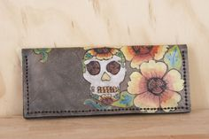 The long and slim Vesa Biker Wallet is a traditionally styled biker wallet with a day of the dead inspired sugar skull and flower pattern on it. This biker wallet comes with the option of a chain to attach it to your belt or a wrist strap for when you are on foot.