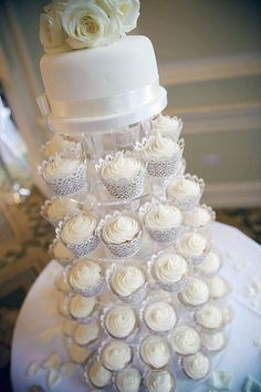 Adorable all-white wedding cupcakes and cake on top #wedding #whitewedding #cupcakes #cake #weddingcupcakes