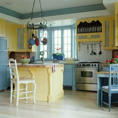 Color-Coordinated Cabinetry- Selecting a different hue for upper and lower cabinets is a great way to help a small kitchen break out of its boxy mold. A sunny yellow keeps the wall cabinets in this kitchen feeling light and airy, while blue base cabinets anchor the room. A yellow island helps balance the color-blocking scheme. Painted crown molding takes the color scheme right up to the ceiling.
