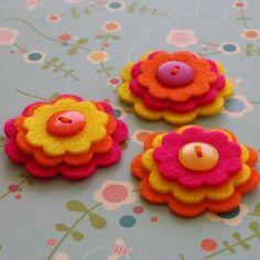 Flores de fieltro en tonos cálidos con botón