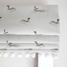 Jumping Hares roman blind with cute pom pom trim