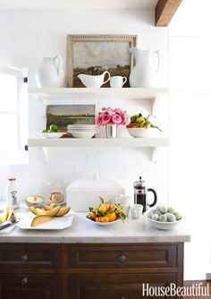 Shelves — instead of wall cabinets — help the small kitchen feel open and give Barrett a place to display shapely pitchers and small-scale paintings. The pale Calacatta Gold marble counter complements white field tiles from Waterworks. - HouseBeautiful.com
