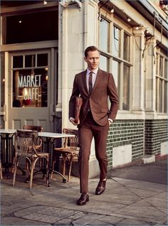 Heading out in London with GQ, Tom Hiddleston wears a brown Gucci made to order suit with a shirt and tie by the Italian label. Hiddleston also sports Church's shoes with a leather Louis Vuitton briefcase.