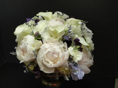 A pastel-inspired bridal bouquet of white and pink peonies. purple throated picasso calla lilies, purple lisianthus, sweet pea, and limonium.   See more wedding bouquets, centerpieces, and more at www.jeffmartinsweddings.com