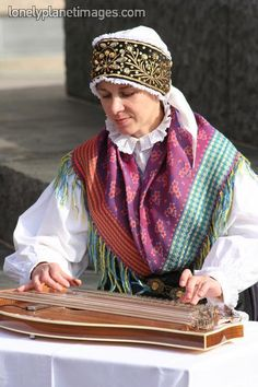 Slovenian folk musician playing zither wearing national dress on Presernov trg.