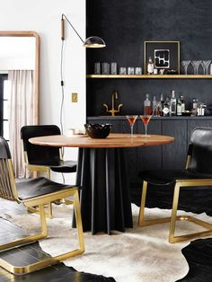 Glamorous black and gold dining room in kitchen with hide rug on Thou Swell @thouswellblog