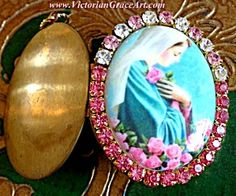 $88 Large vintage rhinestone cameo locket featuring the blessed Mother Virgin Mary as Our Lady of the Mystical Rose. Mary's hands are folded over her chest holding a pink rose. Clear and light and medium pink rhinestones. Inside is copper and brass and can hold 2 photo's and/or your personal prayer petition request.