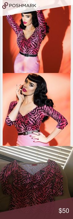 DEADLY DAMES JAILBIRD TOP IN PINK TIGER NWOT, clean, never worn. This top sizzles. Clean,pest free, smoke free home. Show your bad girl curves in this 50s Deadly Dames Jailbird Top!  This top featured a beautiful cut and makes you feel like a real woman! Pleated at the bust for a sexy cleavage and a gorgeous V-neckline which is worn slightly off-shoulder, oh la la! Made from a lovely stretchy, shiny pink fabric with a sassy tiger print. Feel sexy, feel gémine.     3/4 sleeves Pinup Girl…