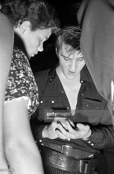 Alfred Wertheimer/Getty Images) Backstage at the Hudson Theatre after his performance on the 'Steve Allen Show,' American musician (and actor) Elvis Presley (1935 - 1977) signs an autograph for a fan, New York, New York, July 1, 1956.