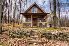 Simple wood plank siding and substantial dark wood door make this small cabin have a much bigger presence.