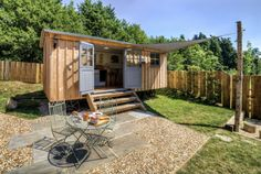 """Surrounded by peaceful, bucolic farmland in Somerset, England, the Shepherds Hut Retreat is comprised of four tiny """"huts"""" available for rent. Each structure overlooks a nearby pond, and includes its own private deck and fire pit. Inside the 20- by eight-foot huts, you'll find a fully functioning kitchen, a bathroom, a dining area, and a built-in bed. Rental rates start from around $243 per weekend.  Look inside the huts."""