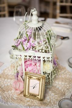 Vintage wedding centerpiece ideas-pastel flowers in birdcage More individual flower arrangements on the outside with lace or burlap table runner
