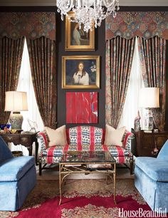 Dramatic dark walls, ikat sofa, a mix of art, energizing patterns & sky blue velvet chairs...