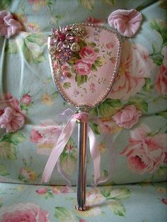 Dressed up old hand mirror with fabric and vintage jewelry.