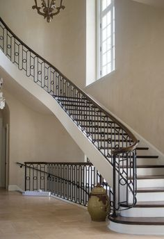 Curved stairs, wrought iron handrail                              …