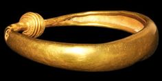 IRON AGE CELTIC GOLD BRACELET WITH TORC FINIALS 600-200 BC  A broad penannular band with rolled edges, c-shaped in section, the 'torc' finials hemispherical with tiered profile, bands of incised rings to the shanks. 37 grams, 79 mm