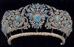What remained after the 'pruning' ordered by Queen Mary in 1912, is the Gloucester Turquoise tiara as we know it today. A large central diamond spray with nine pear-shaped turquoise clustered round a circular stone; flanked by diamond foliate scrolls with circular turquoise as buds and flower heads, and raised above a velvet cushioned band.