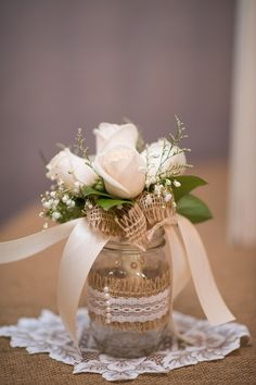 Rose bouquet with elegant ribbon is a nice contrast to the burlap and mason jar.
