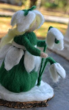 Snowdrop fairy created by needle felting made of a solid wool core using humanely harvested merino and corriedale. She stands approximately 6 in tall on a base of cherry wood.