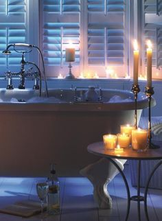 the most PERFECT bathtub of all time. Claw-foot stand-alone tub, the handle, the tray which sits across the tub to hold books, tea, wine, soap, etc... all those candles... Perfect.