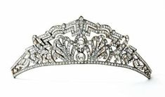 An art deco tiara, circa 1925. A riot of diamond shapes centered on a large circular diamond, flanked by honeysuckle flowers, then topped by a series of of straight geometric lines and arches.