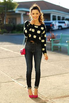 White daisy floral print on a cropped black sweater with anke jeans and fuchsia heels, matching shoulder purse