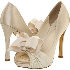Off white high heels with bows on the toes, cute.