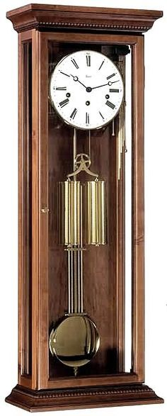 Solid Walnut weight-driven Vienna Regulator clock. Antique walnut case in a satin walnut finish is made of aged wood. This model features beveled front glass, glass side panels and a mechanical 8-day cable-driven Westminster movement. Clean White dial with minute markers. Brass chime rods and separate chime option lever pulls. Bright brass hinges on front door with a magnetic catch. Moving polished brass Pendulum and weights. Made in Germany. Size: H 34 1/2 W 12 5/8 D 6 1/4 inches