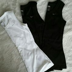 Set of 3 Nike Fitdry tank tops 2 black and 1 white NWOT Nike fitdry tanks. White is pictured more because it photographs better but they are all exactly the same. All have silver a silver embroidered swoosh. Nike Tops Tank Tops