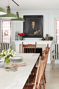 I like the juxtaposition of the antique chairs and marble top table, the picture and industrial overhead hanging pendants, the stripped chairs and the stained glass windows.
