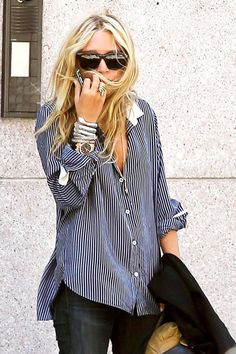 Mary-Kate Olsen wears a blue and white button-down blouse, jeans, stacked jewelry, and black sunglasses
