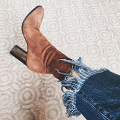 Cropped fringe jeans are paired with tan suede boots