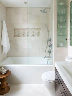 petite salle de bain avec un carrelage beige clair, baignoire douche avec paroi en verre et armoire encastrée au mur