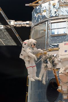 May 14, 2009 – Astronaut John Grunsfeld works on the Hubble Space Telescope while the orbital observatory is anchored to the cargo bay of the Space Shuttle Atlantis.
